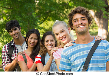 Happy college friends standing in row at campus - Group...