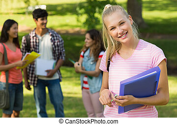 Girl with college friends in background at campus - Portrait...
