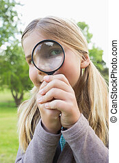 Cute young girl looking through magnifying glass at park -...