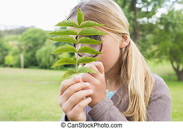 Girl examining leaves with magnifying glass at park - Young...