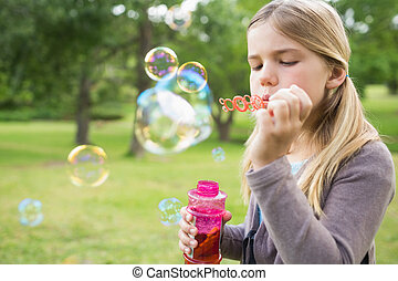 Girl blowing soap bubbles at park - Cute young girl blowing...
