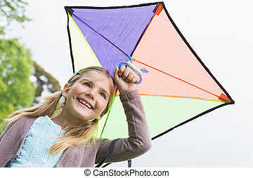 Low angle view of a cute girl with a kite - Low angle view...