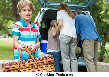 Boy with picnic basket while family in background at car...