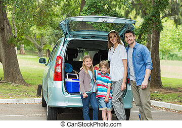 Family of four by car trunk while on picnic - Portrait of a...