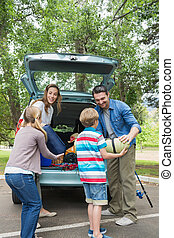 Family unloading car trunk while on picnic - Happy family of...