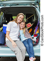 Smiling mother and daughter sitting in car trunk - Portrait...