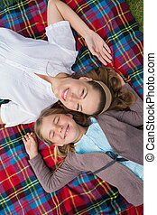 Elevated view of mother and daughter lying at park -...