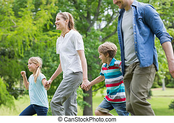 Parents and kids walking in park - Side view of parents and...