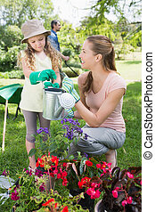 Mother with daughter watering plant