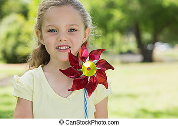 Portrait of cute girl holding pinwheel at park