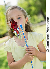 Cute girl holding pinwheel at park
