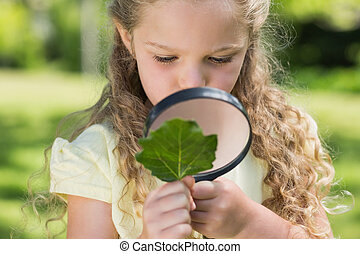 Girl examining leaf with magnifying glass at park - Young...