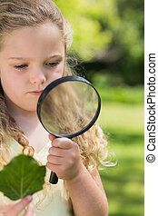 Girl holding leaf and magnifying glass at park - Young girl...