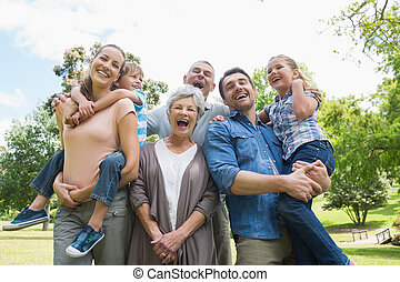 Portrait of cheerful extended family at park - Portrait of...