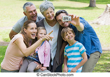 Man taking picture of extended family at park - Man taking...