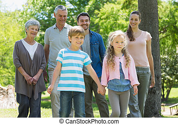 Happy extended family standing at park