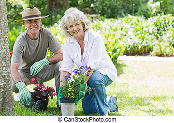 Mature couple engaged in gardening - Portrait of a smiling...