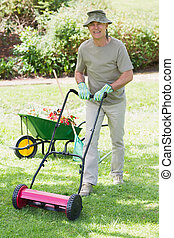 Smiling man mowing lawn - Full length portrait of a smiling...