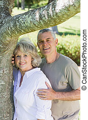 Smiling mature couple besides tree at park