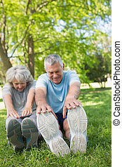 Mature couple stretching hands to legs at park - Full length...