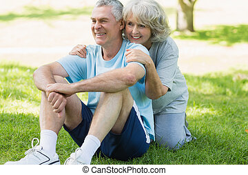 Smiling mature couple sitting on grass at park - Portrait of...