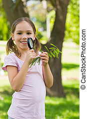Smiling girl holding leaves and magnifying glass at park -...