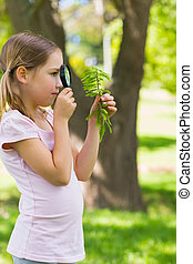 Girl examining leaves with a magnifying glass at park -...