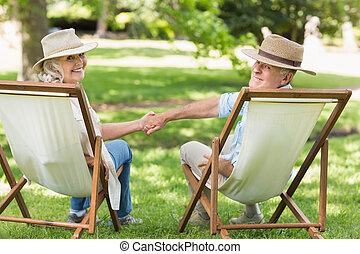 Relaxed mature couple sitting in deck chairs at park - Rear...