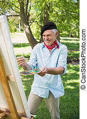 Happy mature man painting in park - Happy mature man...