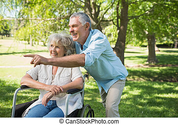 Mature man with woman sitting in wheel chair at park -...