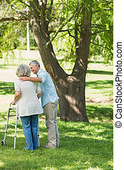 Mature man assisting woman with walker at park - Rear view...