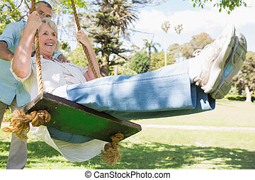 Mature couple at swing in the park - Low angle view of a...
