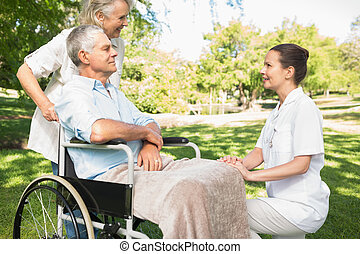 Women with mature man sitting in wheel chair at park - Two...