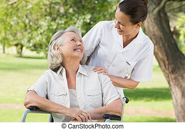 Woman with her mother sitting in wheel chair at park -...