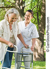 Smiling young female assisting mature woman with walker at...