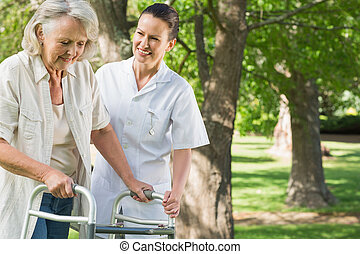 Female assisting mature woman with walker at park - Smiling...