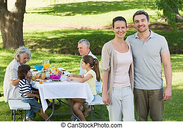 Couple with family having lunch in the lawn - Portrait of a...