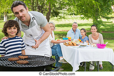 Father and son at barbecue grill with extended family having...