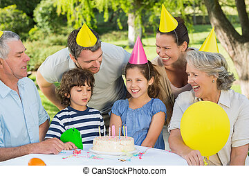 Cheerful extended family wearing party hats at a birthday...