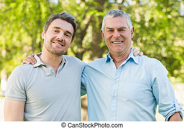 Smiling father with adult son at park - Portrait of a...