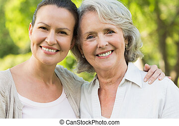 Close-up of smiling mature woman with daughter at park