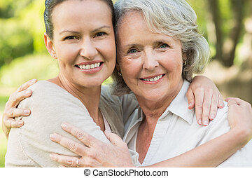 Smiling mature woman with adult daughter - Close-up portrait...