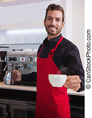 Happy young barista holding jug and cup of coffee in a cafe