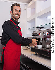 Cheerful young barista making cup of coffee in a cafe