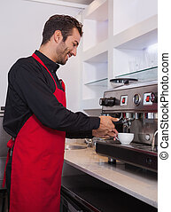 Happy young barista making cup of coffee in a cafe