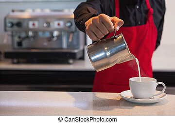 Barista pouring milk into cup of coffee in a cafe