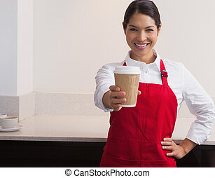 Pretty young barista offering cup of coffee to go smiling at...