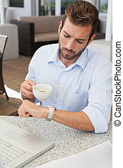 Frowning young businessman checking time holding coffee cup...