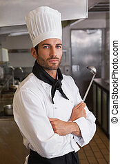 Serious chef looking at camera with arms crossed holding...