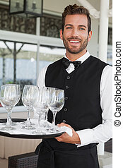 Handsome waiter holding tray of wineglasses in the patio of...